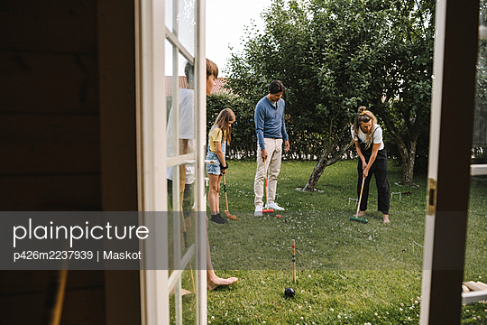 Parents playing polo with children in back yard - p426m2237939 by Maskot