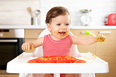 Smiling baby in high chair eating vegetable puree with spoon - p1166m2084900 by Cavan Images
