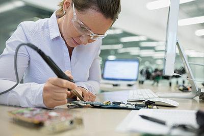 Focused engineer assembling circuit board - p1192m1107869f by Hero Images