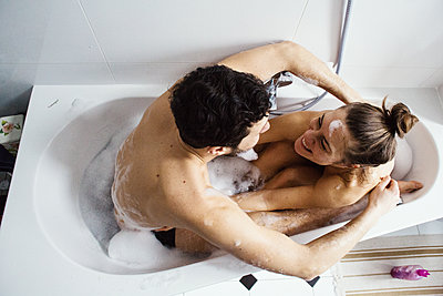 Junges Paar umarmt sich beim Baden und lacht sich an  - p1301m1424732 von Delia Baum