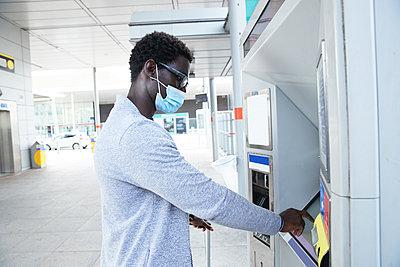 Mature male professional using ticket machine at railroad station during coronavirus - p300m2241046 von Pete Muller