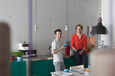 Young gay couple looking away in kitchen - p301m961106f by Halfdark