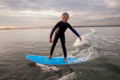 A Boy Surfs At Nahant Beach In Nahant, Massachusetts - p343m1416083 by Laurie Swope