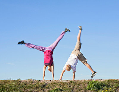 Mid adult couple doing cartwheel in a park - p3741489 by Olli-Pekka Orpo