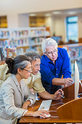 Teacher helping adult students use computer in library - p555m1414257 by Marc Romanelli
