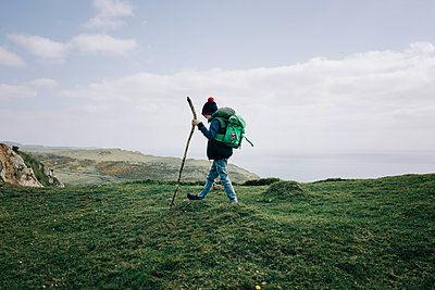 boy hiking along the Jurassic coast with a walking stick exploring - p1166m2279483 by Cavan Images