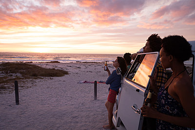 Group of friends relaxing on beach while standing near camper van - p1315m2091178 by Wavebreak