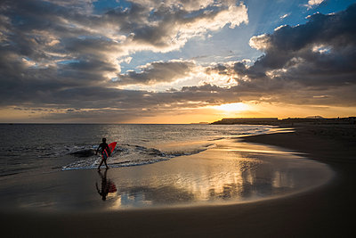 Spain, Tenerife, boy carrying surfboard on the beach at sunset - p300m1189239 by Simona Pillola