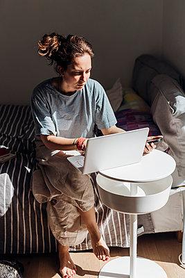 Female freelancer using laptop while sitting on bed - p300m2293676 by Eugenio Marongiu