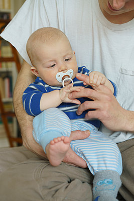 Midsection of father playing with son at home - p301m1148389 by Halfdark