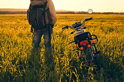 Mari man standing in field with motorcycle - p555m1415812 by Aliyev Alexei Sergeevich