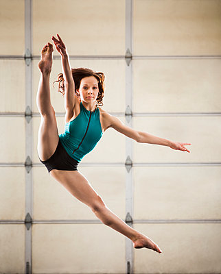 Caucasian dancer leaping in studio - p555m1464224 by Mike Kemp