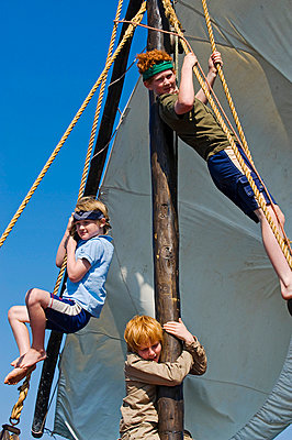 Boys climb the rigging of a dhow while on a cruise around Lake Malawi during a family holiday at Pumulani Lodge - p6521861 by John Warburton-Lee