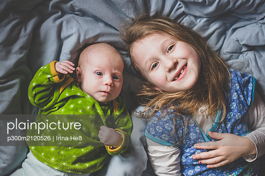 Portrait of smiling little girl lying on bed beside baby girl, top view - p300m2120526 by Irina Heß