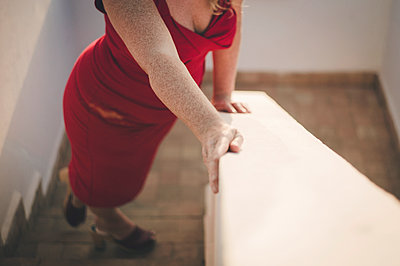 Woman in red dress on the stairs - p1150m1424788 by Elise Ortiou Campion