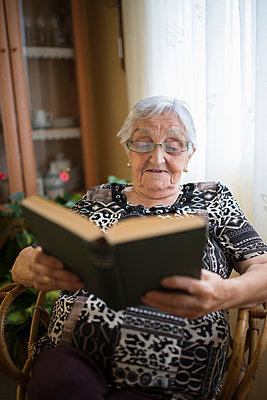 Senior woman reading a book at home - p300m1059038f by Ramon Espelt