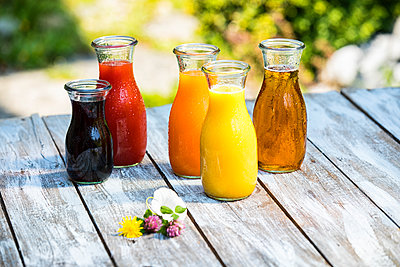 Glass bottles of various fruit juices - p300m2023437 by Roman Märzinger