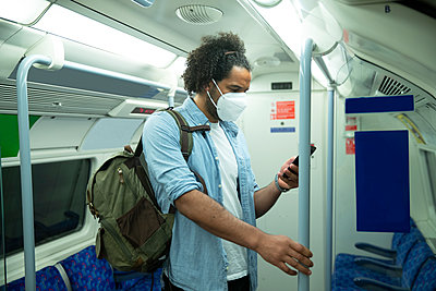 Man wearing protective mask standing in underground train looking at cell phone, London, UK - p300m2202955 by Pete Muller