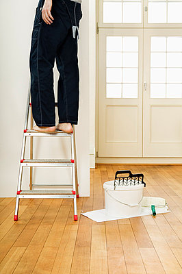 Man on ladder painting wall - p6090292f by DRESDEN photography