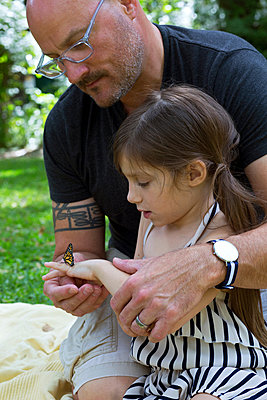 Father and daughter looking at monarch butterfly - p924m1157733 by Kinzie Riehm
