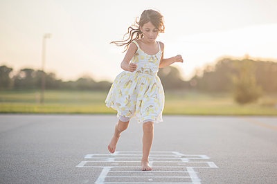 Full length of girl playing hopscotch on footpath against sky - p1166m1230490 by Cavan Images