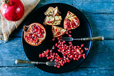 Half of pomegranate, pomegranate seed and two old forks on black plate - p300m1535549 by Kiko Jimenez