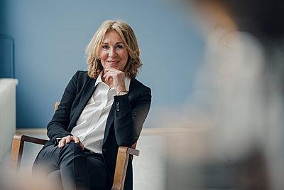 Portrait of smiling senior businesswoman sitting in chair - p300m1587379 by Kniel Synnatzschke