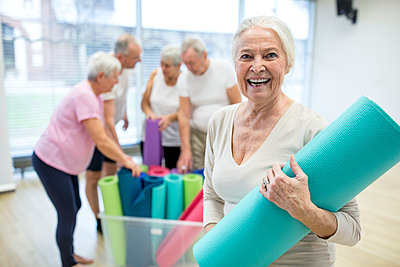 Happy senior woman holding yoga mat after class - p300m2207091 by Fotoagentur WESTEND61