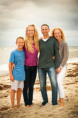Portrait of smiling family at beach - p555m1231795 by Stephen Simpson Inc