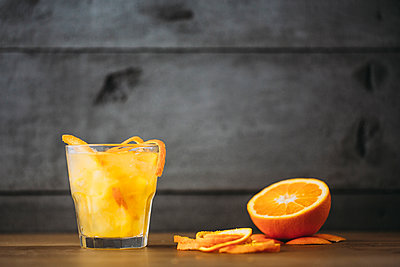 Orange juice with peel and sliced fruit - p555m1412922 by Lumina Images