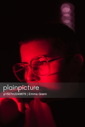 Young woman in red light, portrait - p1507m2249879 by Emma Grann