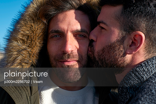 Close-up of man kissing on boyfriend's cheek wearing hood - p300m2256702 by Veam