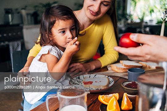 Man giving fruit to daughter having breakfast at home - p300m2293281 by Angel Santana Garcia