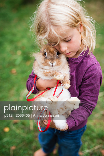 Girl hugging rabbit - p312m2086405 by Anna Johnsson