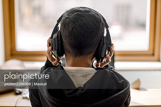 Rear view of boy with headphones at home - p426m2296368 by Maskot