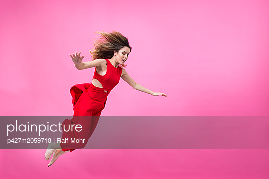 Woman in red dress mid-air - p427m2059718 by Ralf Mohr