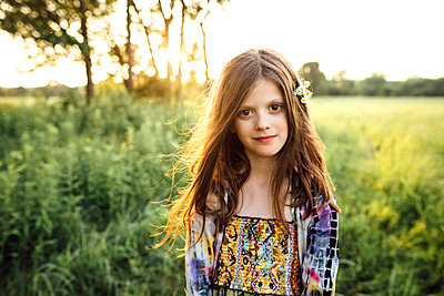 Portrait of girl standing on grassy field - p1166m1182582 by Cavan Images