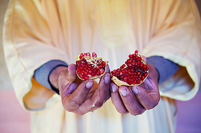 Man holding pomegranate in his hands - p1167m2269949 by Maria Schiffer