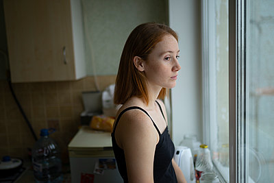 Young woman looking out of window - p1646m2253841 by Slava Chistyakov