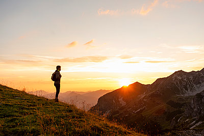 Germany, Bavaria, Oberstdorf, man on a hike in the mountains looking at view at sunset - p300m2028803 by Daniel Ingold