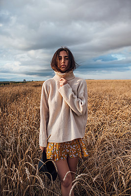 Portrait of young woman wearing oversized turtleneck pullover standing in corn field - p300m2063010 by Vasily Pindyurin