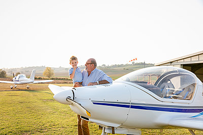 Grandfather picking up grandson while standing at airfield - p300m2220947 by Emma Innocenti