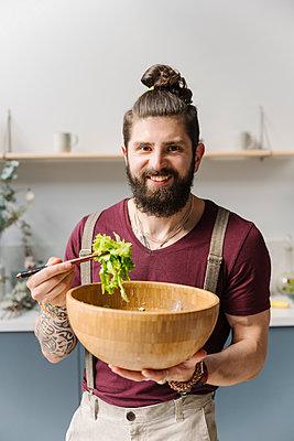 Bearded man smiling while holding salad bowl at home - p300m2287604 by Ekaterina Yakunina
