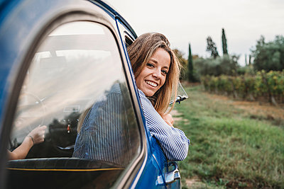 Woman sticking head out of car window - p429m2097688 by Lorenzo Antonucci