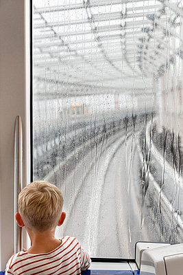 Boy looks through window with raindrops - p756m2122766 by Bénédicte Lassalle