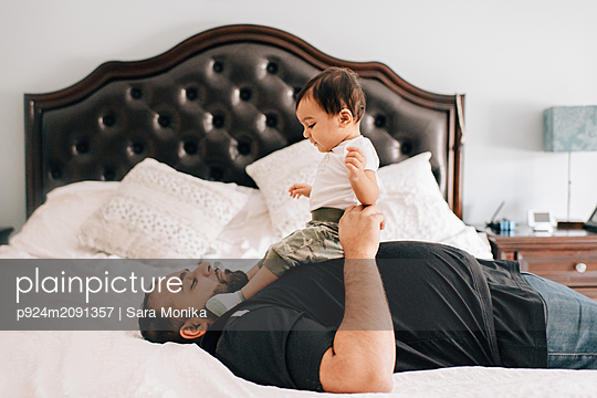 Father lying on bed with baby son on his chest - p924m2091357 by Sara Monika