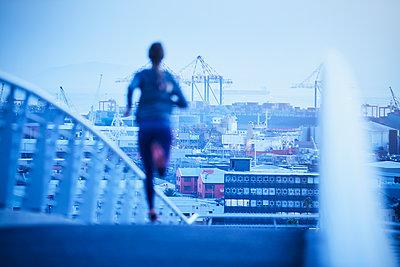 Female runner running on urban footbridge at dawn - p1023m1201842 by Ryan Lees