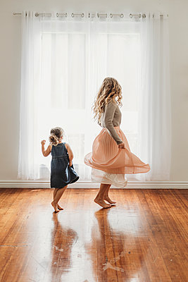Mother and young daughter dancing in studio - p1166m2130789 by Cavan Images