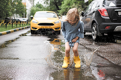 Girl wearing blue dress and rubber boots, jumping in pond on street, yellow car in the background - p300m2083354 by Ekaterina Yakunina