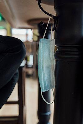 Mask hanging under restaurant table - p300m2242814 by Ezequiel Giménez